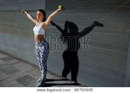 Young woman in sporty clothing training bicep curls while lifting weights on copy space background