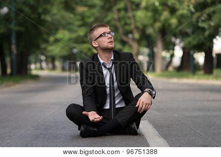 Businessman Sitting On Asphalt Begs For Money