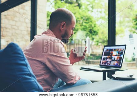 Modern business man connecting to wireless on his laptop computer during coffee break