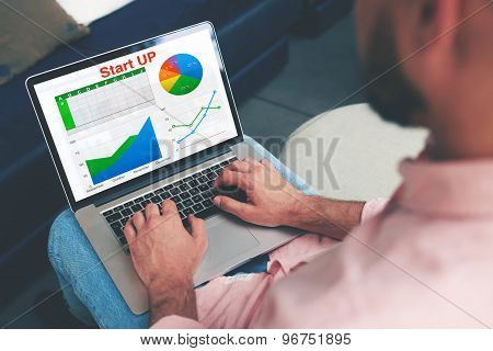 Businessman looking at financial data with graphics and charts while work on a laptop computer