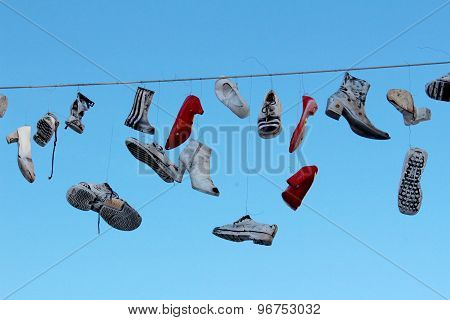 Shoes hanging from wire in mid air