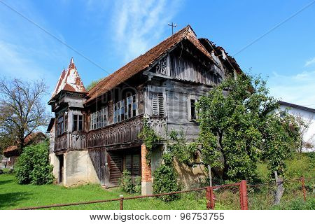 Very old broken wooden house covered in green plants