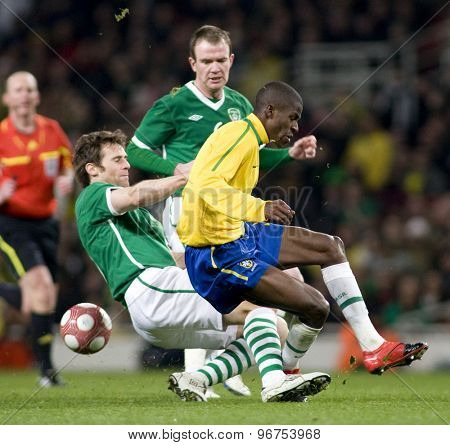 LONDON, ENGLAND. March 02 2010: Ireland's Kevin Kilbane fouls Brazils Maicon during the international football friendly between Brazil and the Republic of Ireland played at the Emirates Stadium.