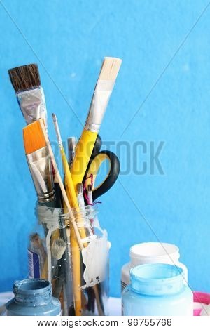 Paintbrushes in glass jar and open container of colors