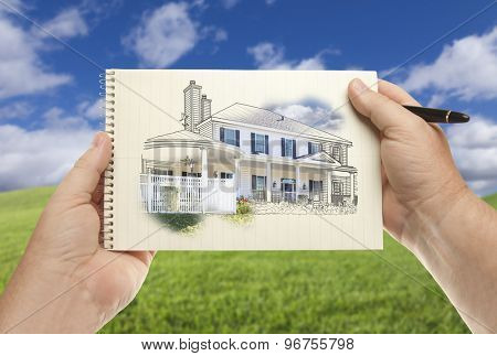 Male Hands Holding Pen and Pad of Paper With House Drawing Over Empty Grass Field and Sky.