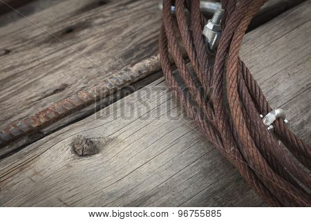 Abstract Rusty Aged Iron Cable Laying on Old Wood Planks.