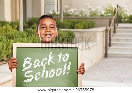 Happy Hispanic Boy Holding Back to School Chalk Board Outside on School Campus.