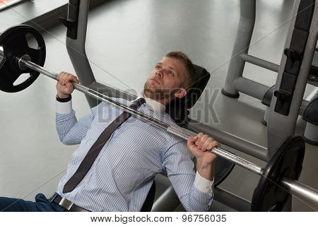 Healthy Young Businessman Doing Bench Press Exercise