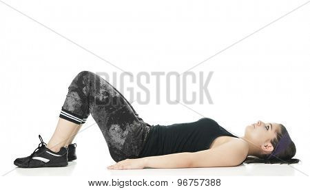 A pretty teen girl in her black and gray workout clothes, her back and arms flat against the floor, her knees bent.  On a white background.