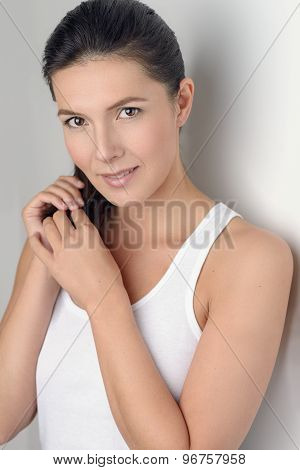 Woman Smiling At The Camera While Holding Her Hair
