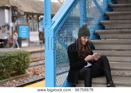 Latin Woman Talking On The Phone In The Train Station