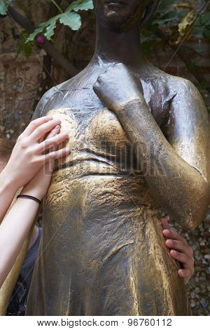 VERONA, ITALY - JULY 13: Cropped shot of two hands holding right breast of bronze Juliet statue. July 11, 2015 in Verona. Holding the worn out breast is said to bring good luck with love matters.