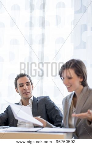 Young Male And Female Business People In Corporate Attire Discussing Some Plans