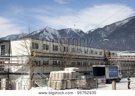 GARMISCH PARTENKIRCHEN, GERMANY. Feb 01 2011: Paraglider pilots fly over the construction site of the offices for the TV and organisers preview images for the 2011 Alpine skiing World Championships
