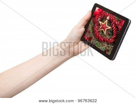 Hand Holds Tablet Pc With Red Star And Tinsel