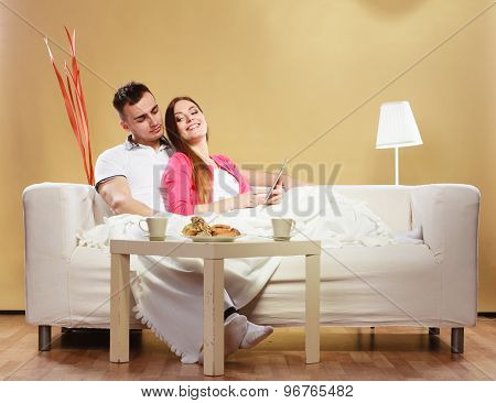 Couple Reading Ebook Relaxing At Home On Sofa.