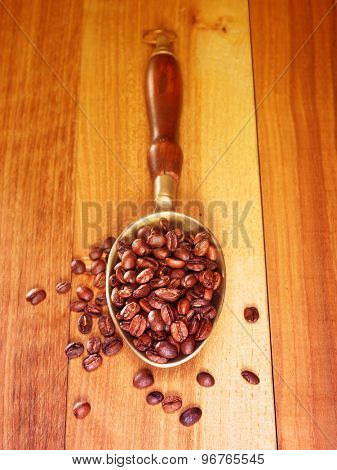 Coffee beans on wooden board with metal scoop. Filtered image: vintage effect.