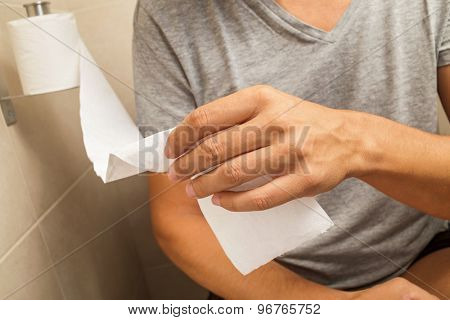 detail of a young caucasian man in the toilet getting some paper from the roll