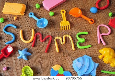 the word summer made from modelling clay of different colors and some beach toys such as toy shovels and sand moulds, on a rustic wooden surface