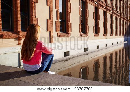Rear view young female looking thoughtful as sitting on the steps alone outdoors