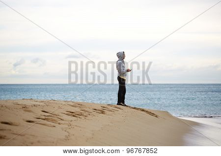 Male runner having a rest after run while enjoying beautiful sea landscape view outdoors