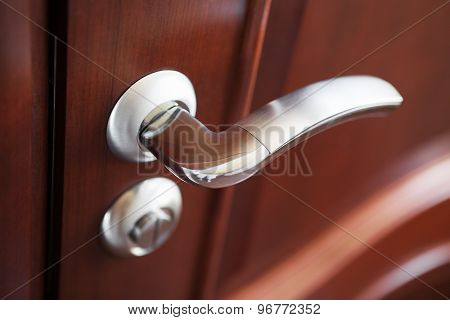 The Metal Door Handle On A Brown Door