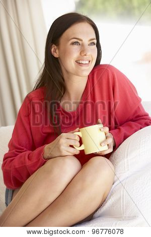 Young Woman Relaxing At Home With Hot Drink