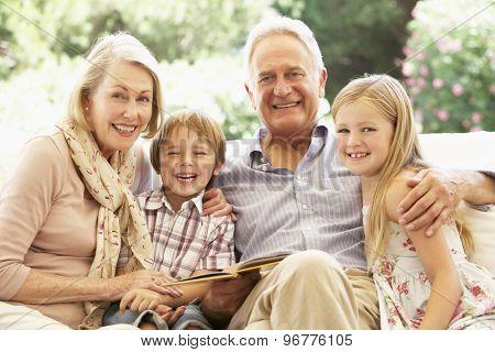 Portrait Of Grandparents Reading To Grandchildren On Sofa