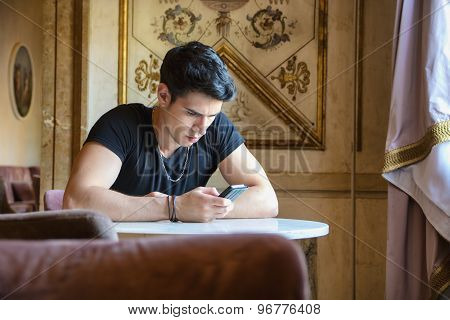 Young man in elegant place using cell phone