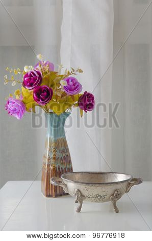 Moroccan Metal Bowl Placed On A Table With A Vase Of Flowers.