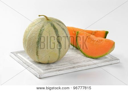 fresh cantaloupe melon on wooden cutting board