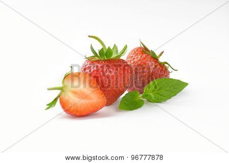 two and half fresh strawberries on white background