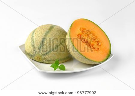 close up of halved cantaloupe melon on white plate