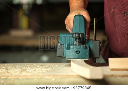 Carpenter Working With Electric Planer.