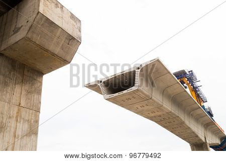 Construction of a LRT train bridge in progress with sections of it being attached.