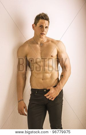 Handsome topless muscular man standing, studio shot