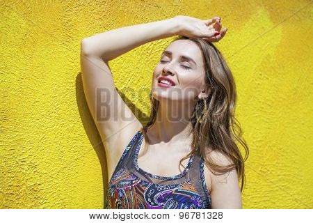 Beautiful young woman in colorful dress, against yellow street wall