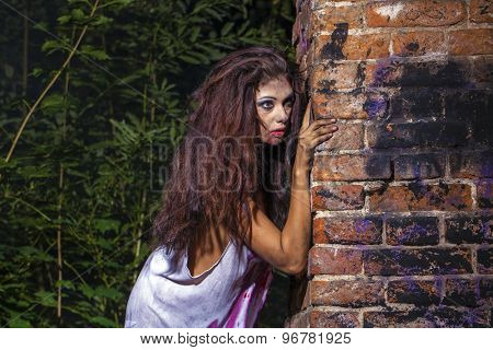 Sinister woman in a bloody shirt on dark brick wall
