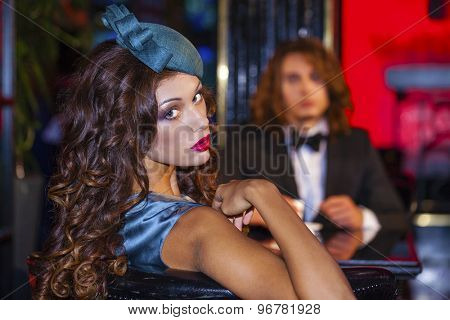 Strong young couple sitting in a nightclub at the table