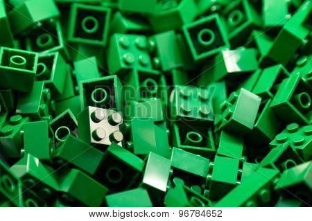 Pile of green color building blocks with selective focus and highlight on one particular block
