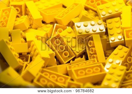 Pile of yellow color building blocks with selective focus and highlight on one particular block