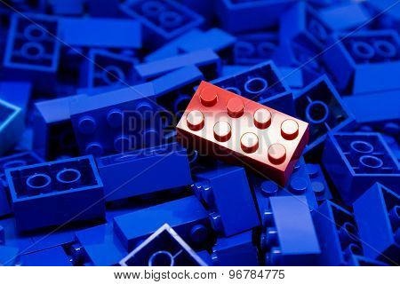 Pile of blue color building blocks with selective focus and highlight on one particular red block
