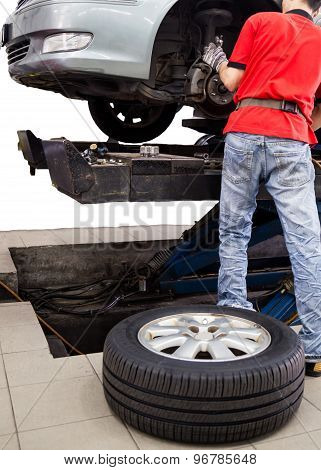 Mechanic repairing the wheel area of a vehicle in a workshop