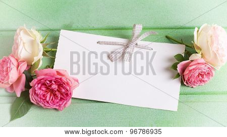 Fresh Pink Roses And Empty Tag  On Green Wooden Background.