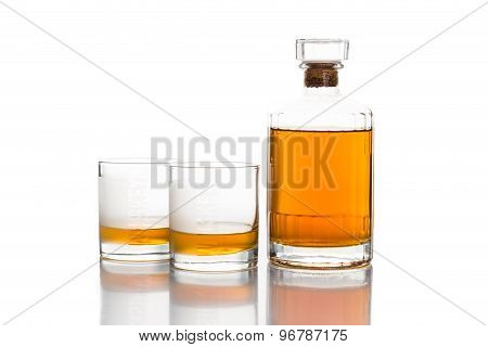 Whiskey bottle with two glasses of whiskey on neat isolated in white