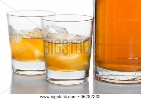 Two glasses of whiskey on the rocks and a whiskey bottle isolated in white