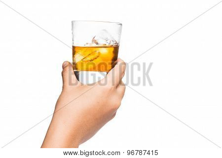 Hand holding a glass of whiskey on the rock proposing a toast