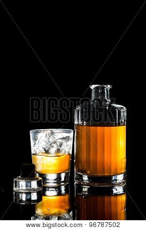 Whiskey on the rocks and a bottle of whiskey with cork on table in dark background in portrait