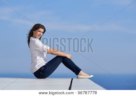 relaxed young beautiful woman in front of luxury modern home villa  on balcony on sunny day