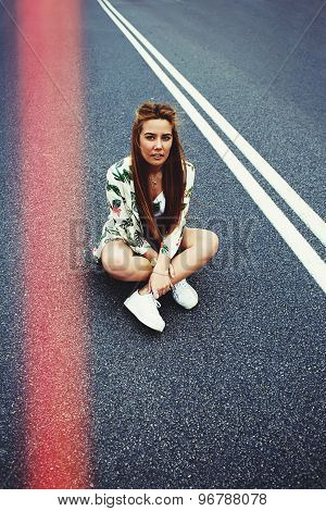 Attractive Californian hipster girl sitting on her cruiser longboard in the middle of asphalt road